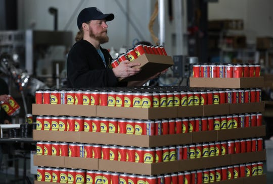 Derek Armstrong, a brewer at Three Heads Brewing in Rochester, stacks a new beer, Lancers Kickin Lager, from the canning line. Three Heads has other new beers that can't be distributed until the government shut down is ended.
