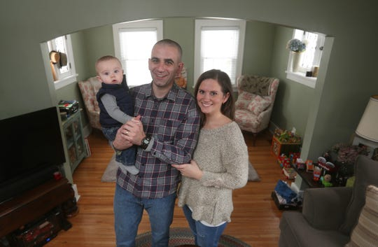 Millennial home buyers Mark and Lynne Van Thof with their son Henry in their Fairport home.