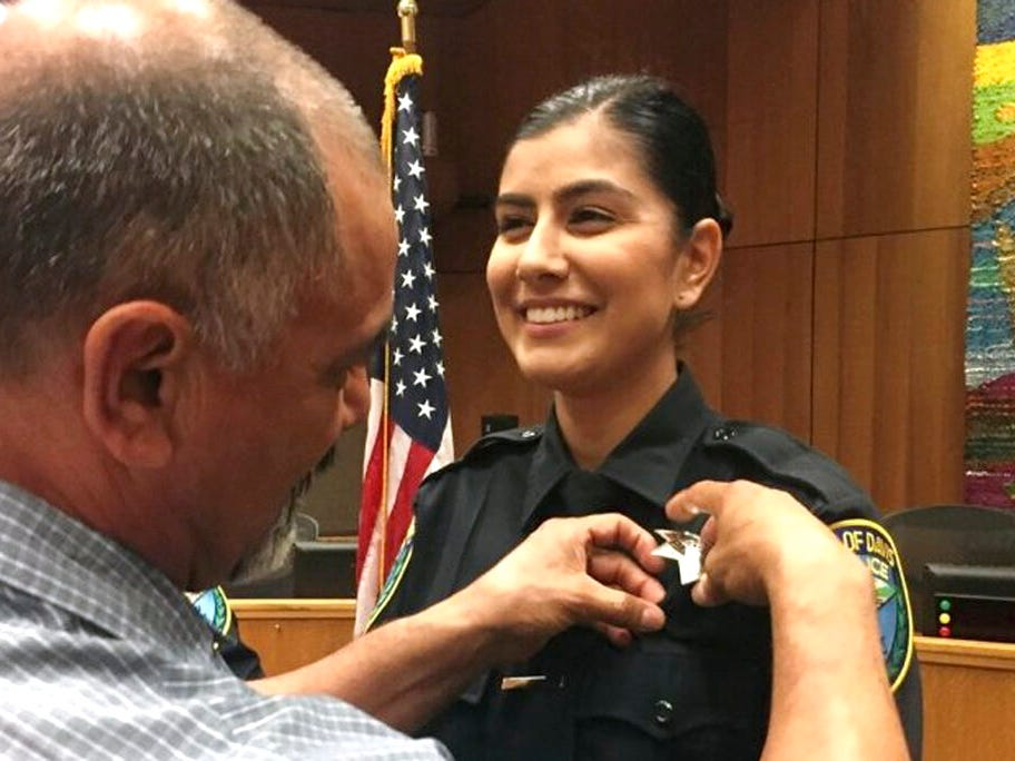 This Aug. 2, 2018, photo provided by Williams Pioneer Review shows Merced Corona, left, pinning his daughter Natalie Corona's badge on her uniform during a swearing-in ceremony in Davis, Calif. Natalie Corona was shot and killed during a routine call Thursday, Jan. 10, 2019.
