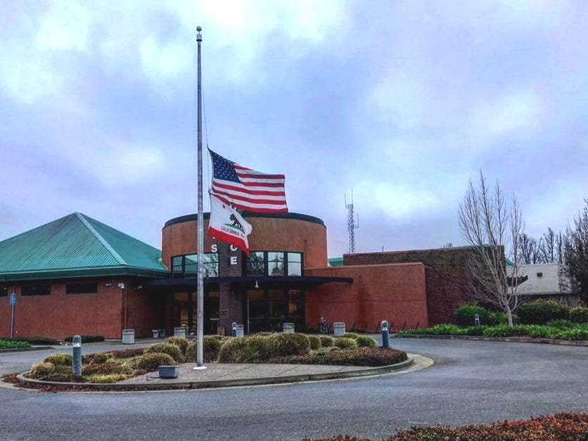 Flags fly at half-staff Friday outside the Davis Police Department to honor 22-year-old rookie officer Natalie Corona who was shot and killed Thursday night.