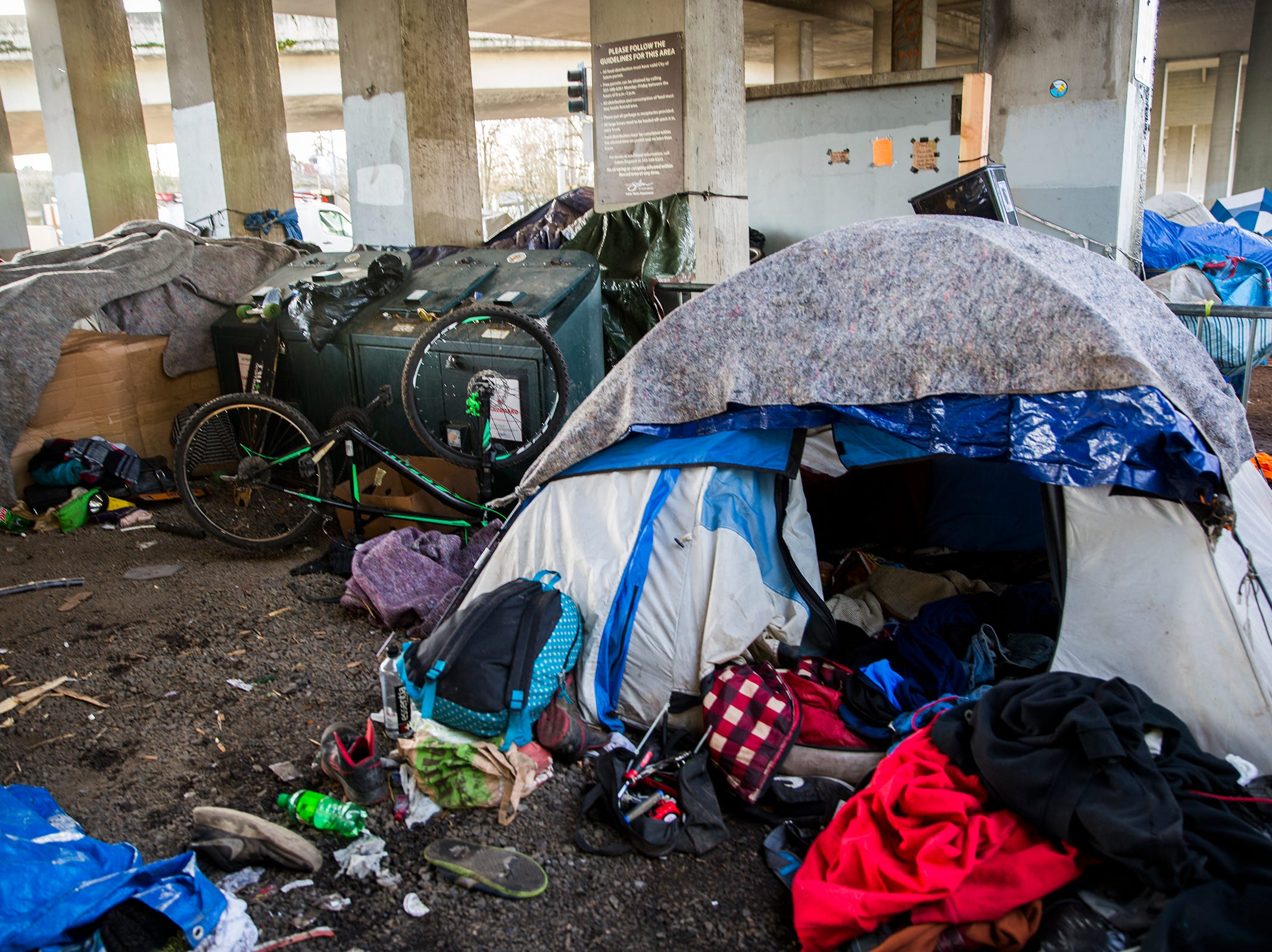 Tents and belongings crowd the edge of Marion Square Park under the Marion St. Bridge on Front St. NE in Salem on Thursday, Jan. 10, 2019.