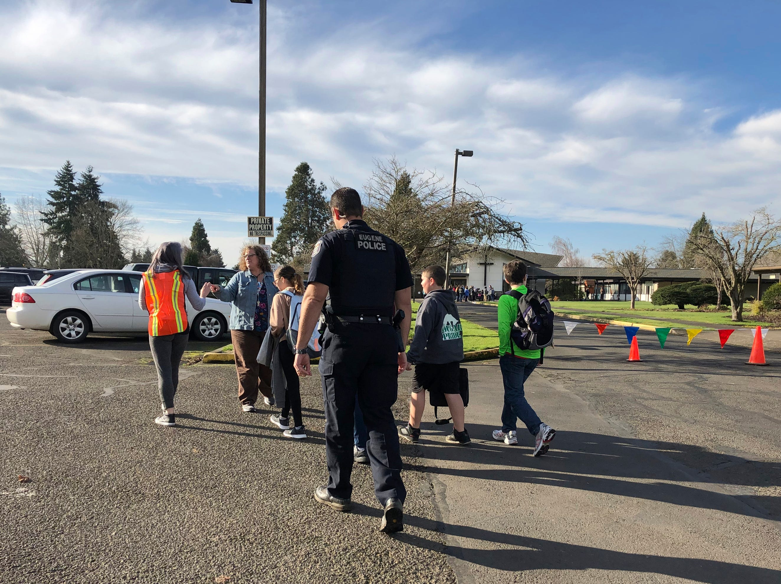 Eugene police officers and teachers escort students at Cascade Middle School to be reunited with their waiting parents outside St. Mark's Catholic Church in Eugene, Ore., Friday, Jan. 11, 2019.