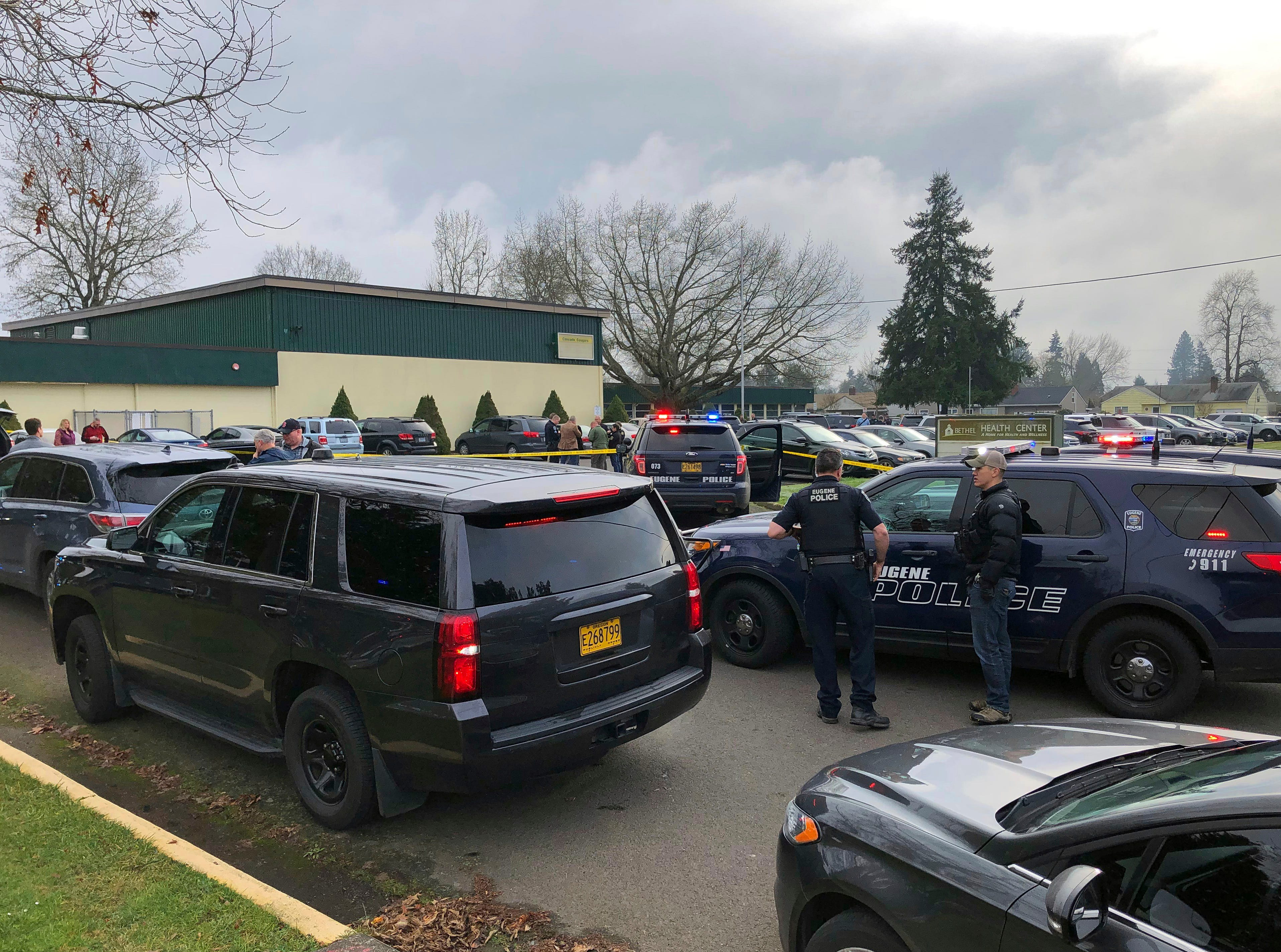 Police officers work the scene where a suspect was shot at a Cascade Middle School in Eugene, Ore, on Friday, Jan. 11, 2019.