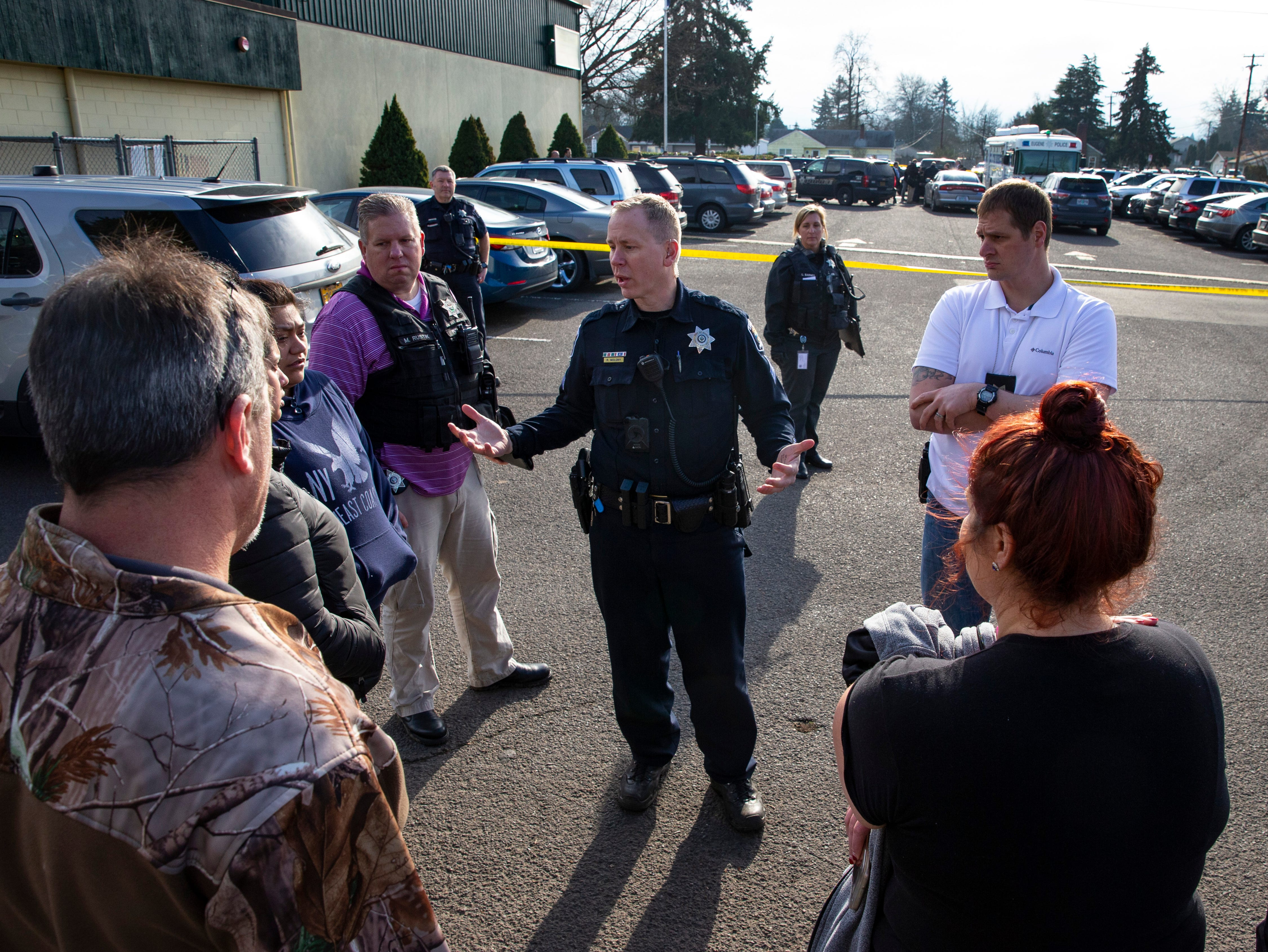 Eugene Police Sgt. Ryan Molony, center, talks to parents outside Cascade Middle School in Eugene, Ore. after a shooting, Friday Jan. 11, 2019.
