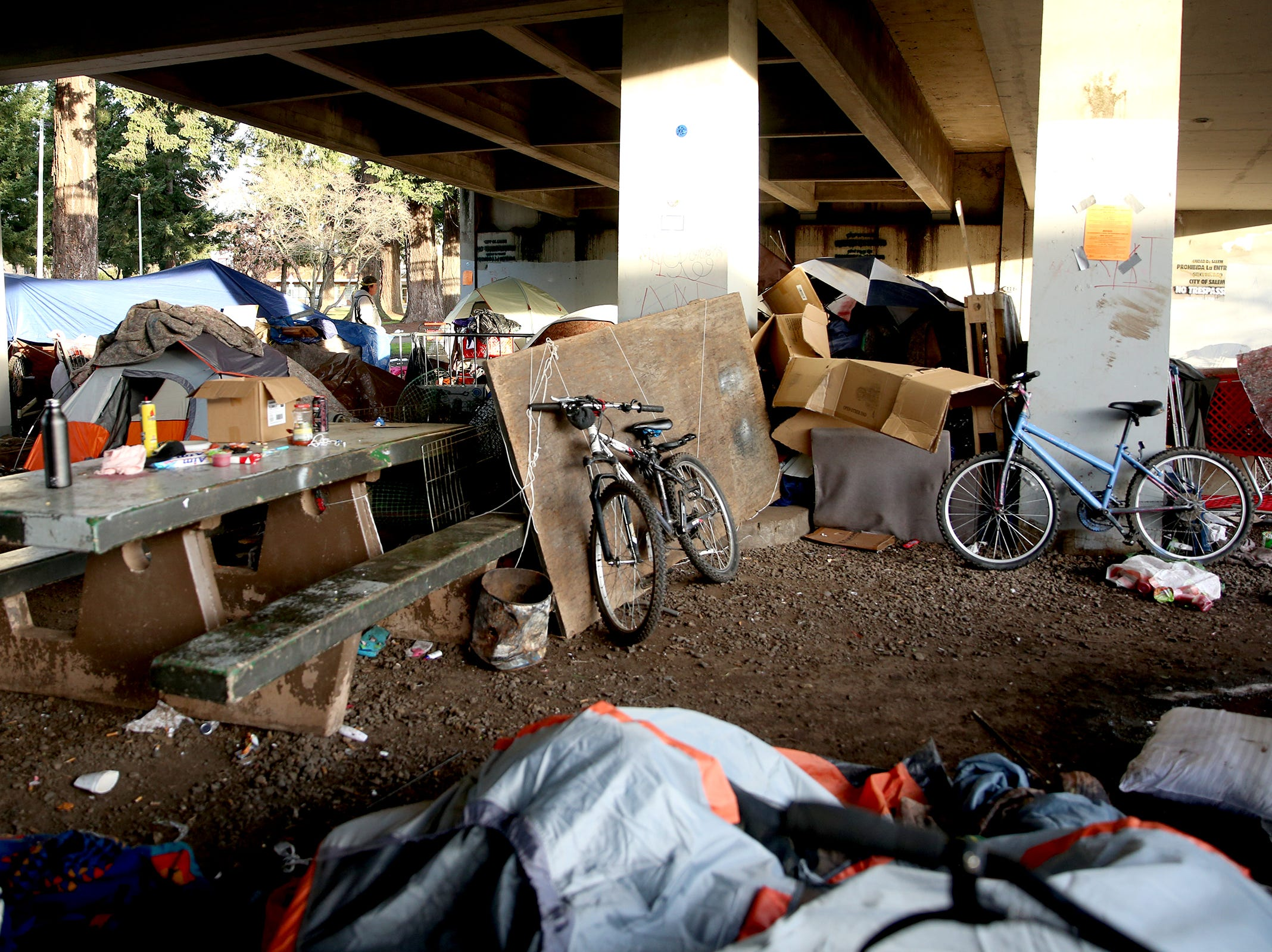 Bikes, personal belongings and trash crowd the edge of Marion Square Park under the Marion St. Bridge on Front St. NE in Salem on Thursday, Jan. 10, 2019.