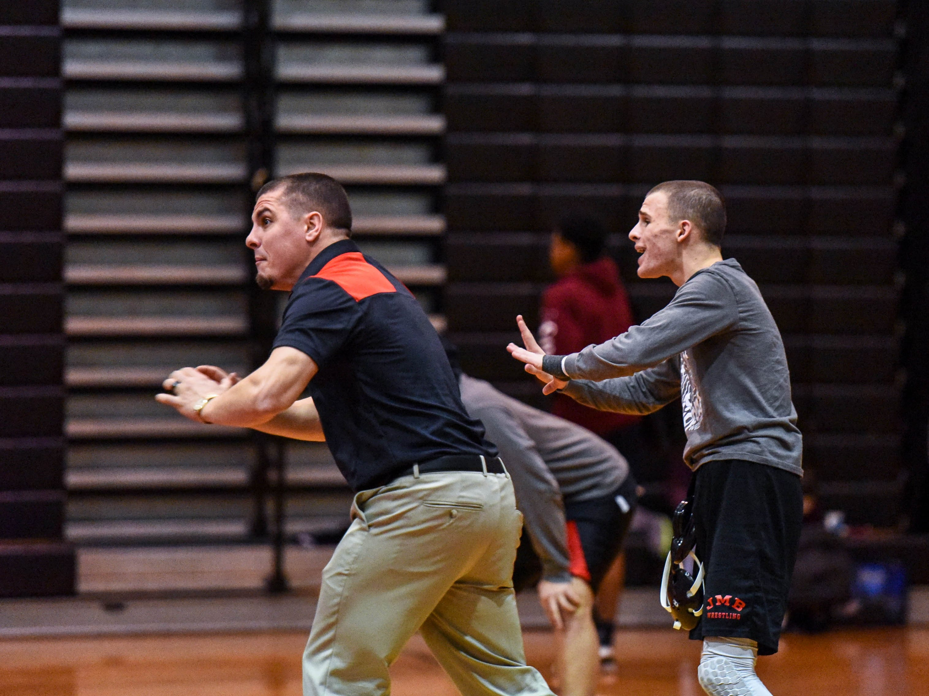 Bennett coach Justin Bradley and wrestler Patrick Hugues yell instructions during the team's match against Kent Island's at Bennett High on Wednesday, Jan 9, 2018.