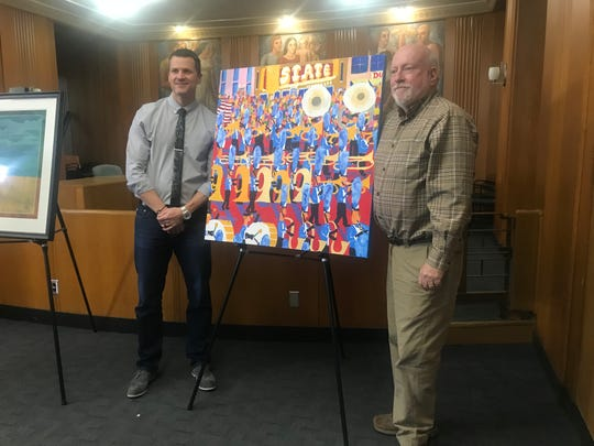 "Sioux Falls-based artist Rodger Ellingson and Mayor Paul TenHaken pose for photographs next to Ellingson's ""The Band,"" a bright, colorful canvas painting depicts the Festival of Bands with musicians marching in front of the State Theater."
