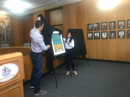 "Mayor Paul TenHaken and Sioux Falls Art Council's Angelica Mercado unveil ""Looking at North Dakota,"" an art piece by the late Robert Aldern that will be displayed in the mayor's office for the next several months."
