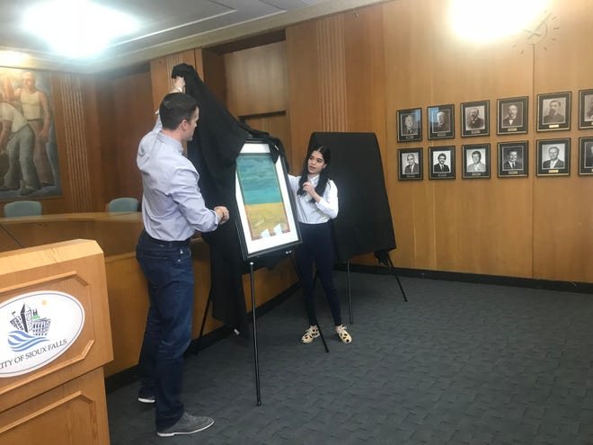 """Mayor Paul TenHaken and Sioux Falls Art Council's Angelica Mercado unveil """"Looking at North Dakota,"""" an art piece by the late Robert Aldern that will be displayed in the mayor's office for the next several months."""