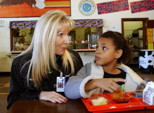 In 2003, York Elementary School Principal Natalie Cauldwell visits with Kitina Dickson during lunch.