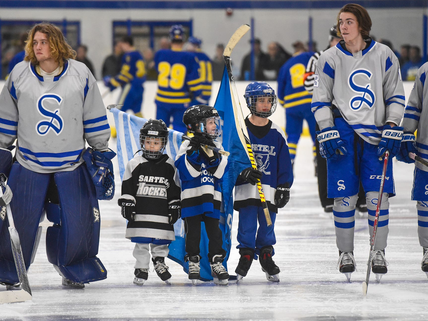 Youth hockey players line up with the Sartell varsity team before the start of the Thursday, Jan. 10, game at Bernicks Arena in Sartell.