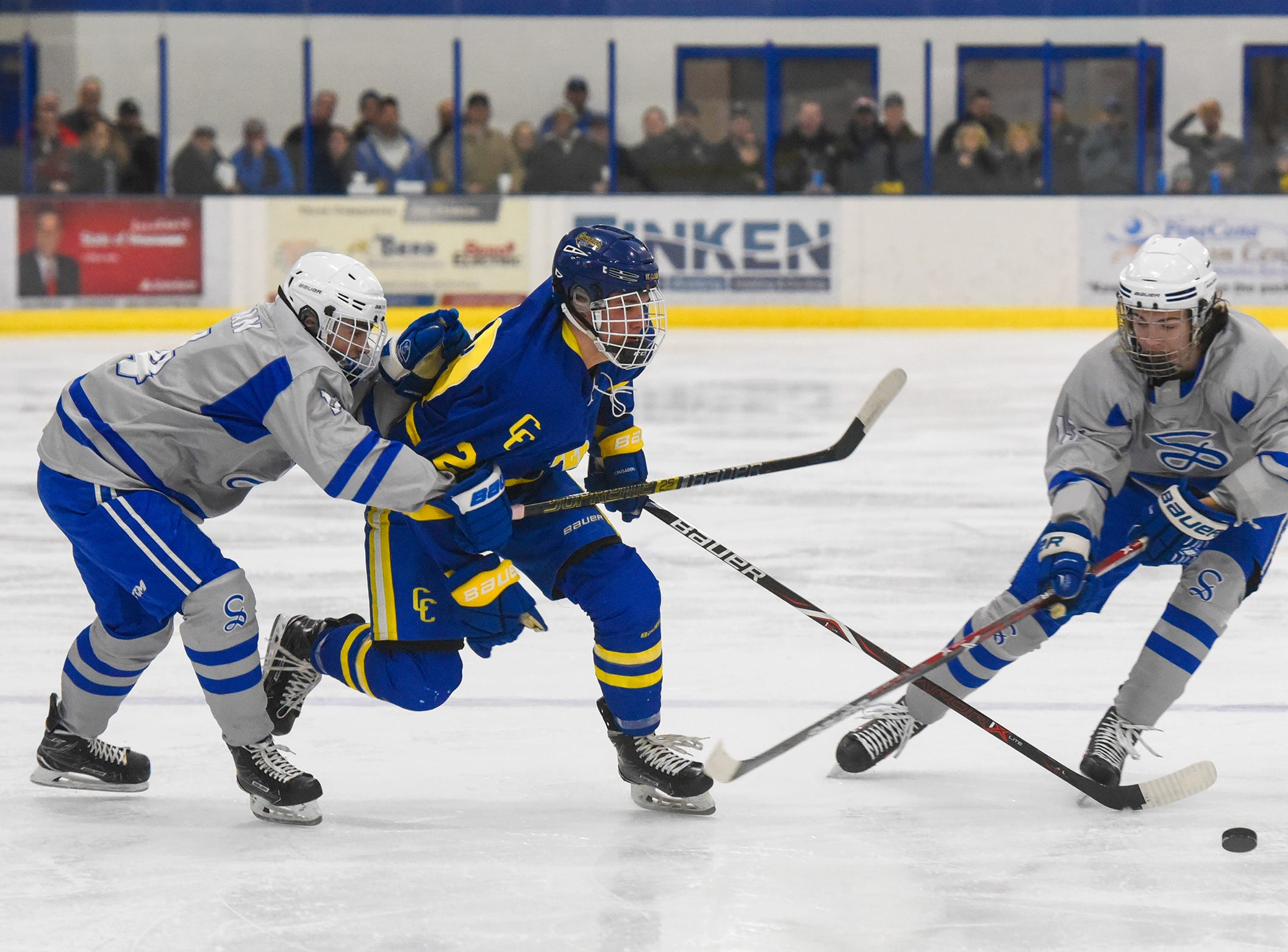 Cathedral's Jackson Savoie cuts between Austin Adelman and Tyan Zulkosky of Sartell during the Thursday, Jan. 10, game at Bernicks Arena.