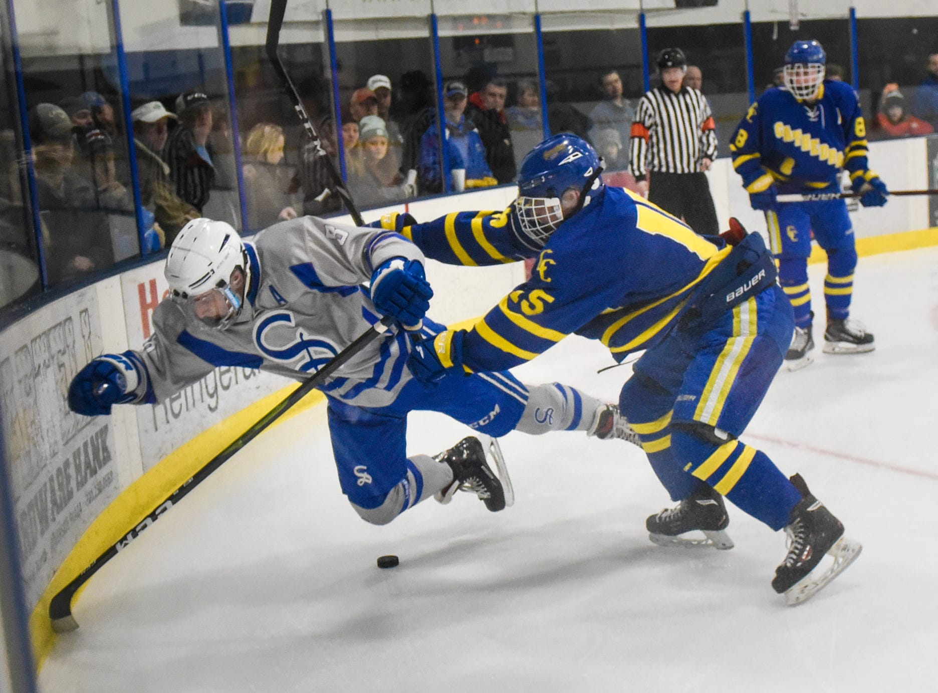 Connor Kalthoff of Sartell and CJ Zins of Cathedral battle along the boards during the Thursday, Jan. 10, game at Bernicks Arena in Sartell.