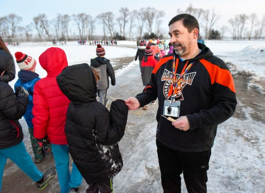 Physical education teacher George Bienusa hands students a popsicle stick for each lap they complete while walking before school Friday, Jan. 11, at Clearview Elementary School in Clear Lake.