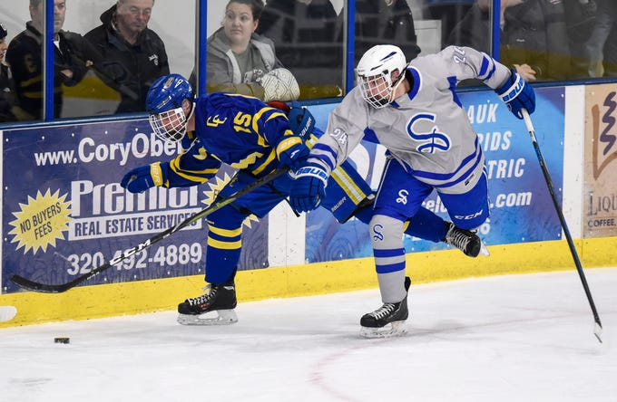 CJ Zins of Cathedral and Sartell's Nick Plautz struggle for control of the puck during the Thursday, Jan. 10, game at Bernicks Arena in Sartell. The Crusaders beat Sartell, 5-1. Visit www.sctimes.com/sports to see more photos of the game.