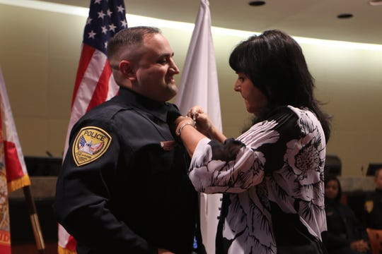 Christopher Fariello's badge is pinned by a family member Friday. He is one of 11 new Tallahassee Police officers