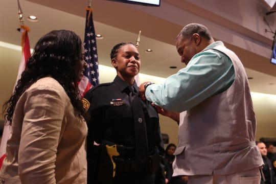 Brook'Lyn Burns has her badge pinned by her family as she is sworn in as a Tallahassee Police officer