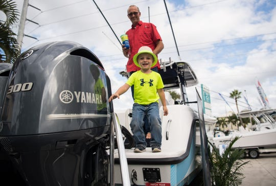 """Dean Nicholson, 3, steps off a boat ahead of his grandfather, Scott Keiper, both of Port St. Lucie, at the 45th annual Stuart Boat Show on Friday, Jan. 11, 2019, in Stuart. """"I actually came here to look at the boats, and to talk to Paul, who's the owner of Bluewater (Sportfishing Boats),"""" Keiper said. """"I have a 2850 and I want to change couple things, so no better place to talk to the owner than here."""""""