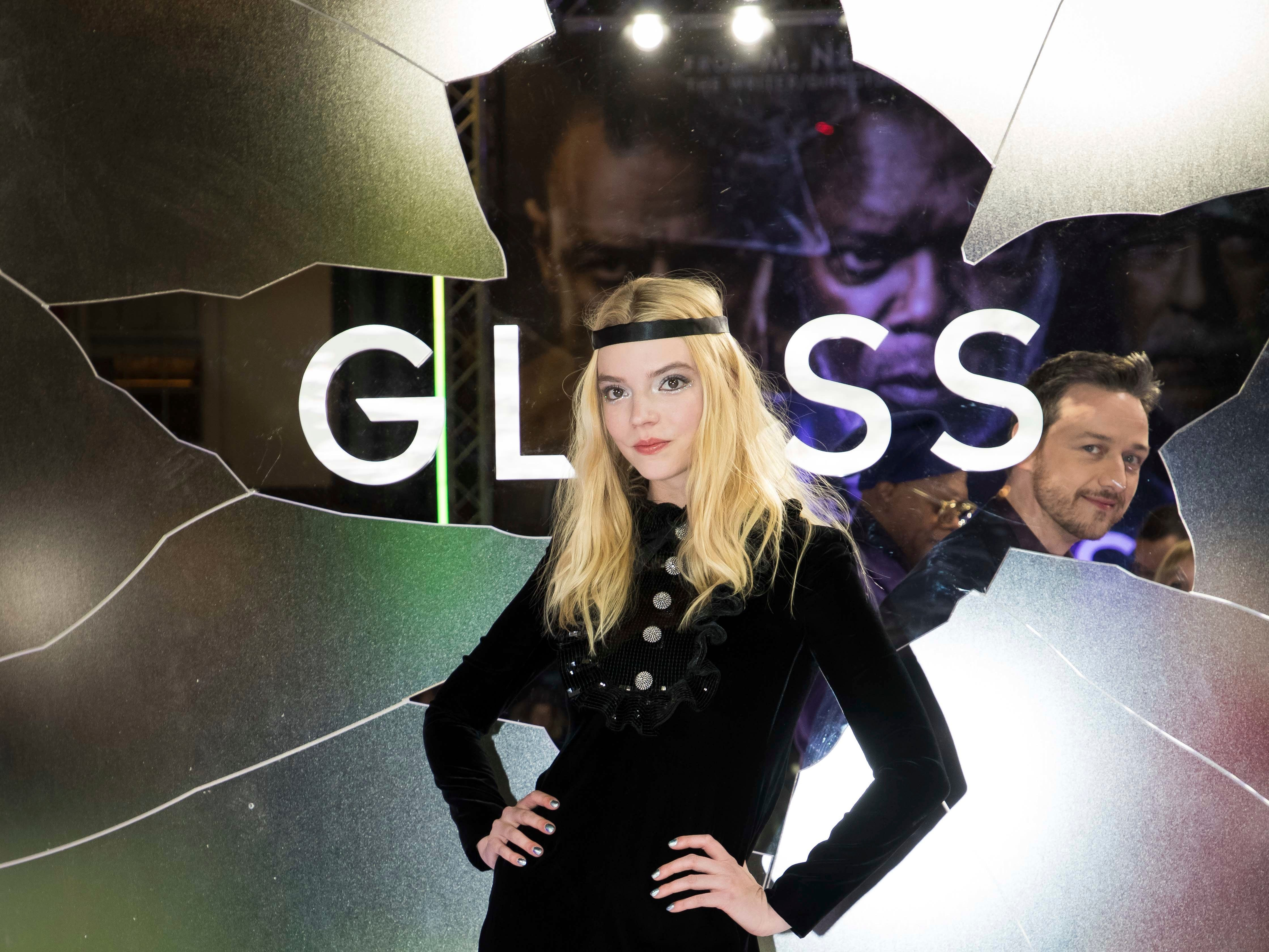 """Actress Anya Taylor-Joy, foreground, poses for photographers upon arrival at the premiere of the film """"Glass"""" in London, with fellow actor James McAvoy looking on, Wednesday, Jan. 9, 2019."""