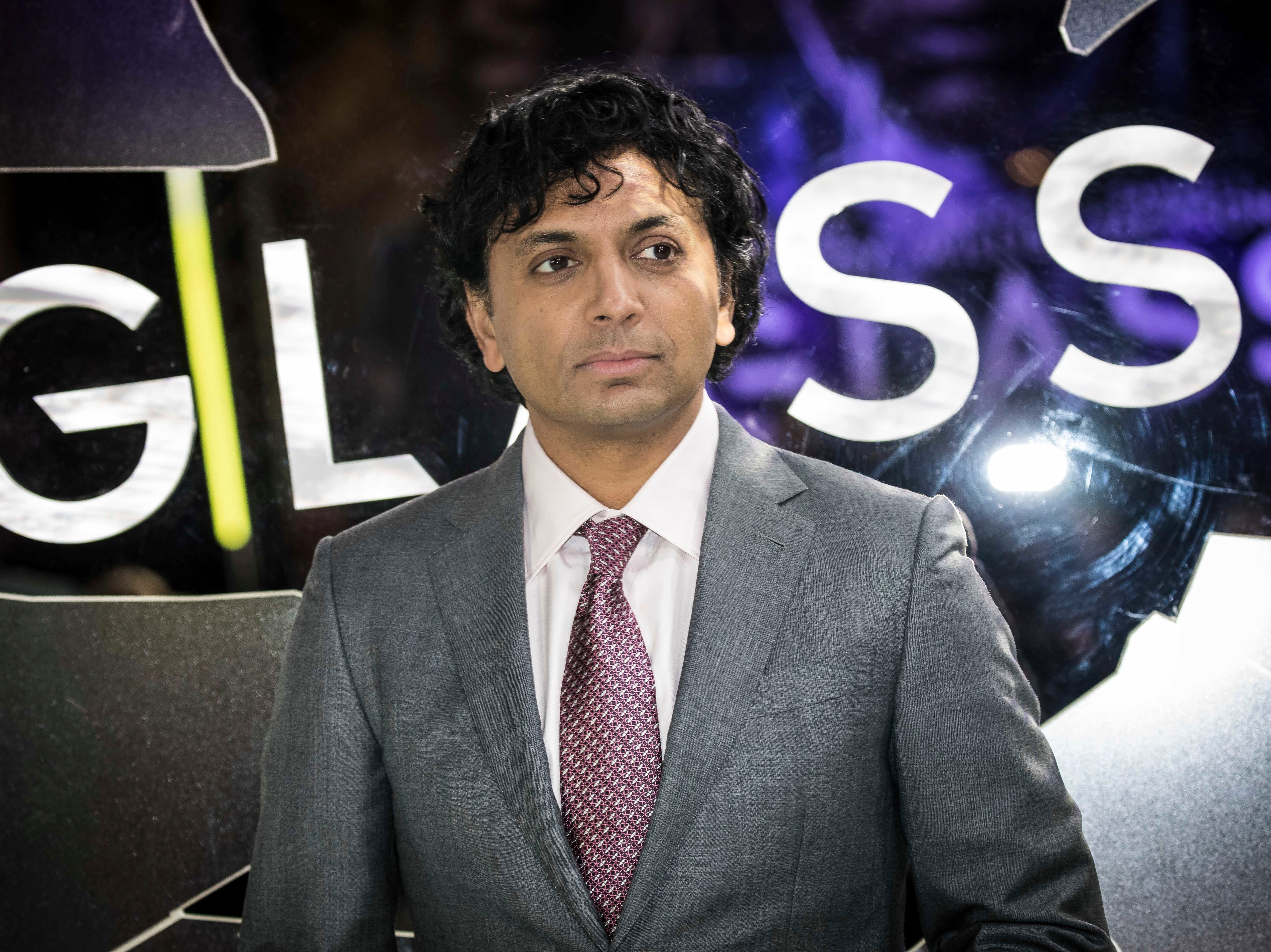 """Director M. Night Shyamalan poses for photographers upon arrival at the premiere of the film """"Glass"""" in London on Wednesday, Jan. 9, 2019."""