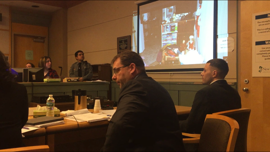 Defendant Jeremiah E. Monell (seated, right) watches his son testify against him on Thursday in Cumberland County Superior Court. Monell is charged with first-degree murder in the death of Tara O'Shea-Watson in 2016. The son, now 14, is using a laser pointer to point out features of his bedroom, from where he said he watched his father kill his mother. Next to Monell is his one of his attorneys, Nathan Perry.