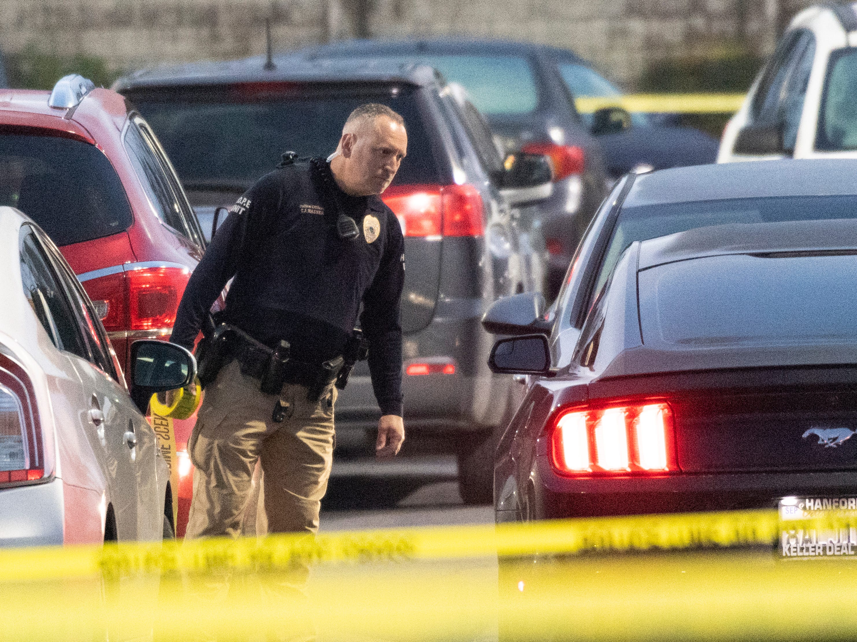 Visalia Police officers preserve the scene, including a handgun on the ground, of an officer-involved shooting in the north parking lot of Visalia Mall on Thursday, January 10, 2019.