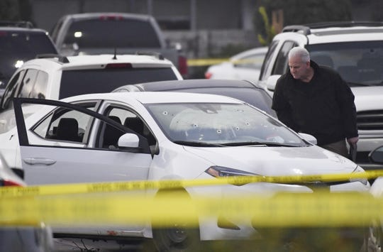 A detective looks into a white Toyota Corolla riddled with bullets after reports of shots fired near the Visalia Mall on Thursday, January 10, 2018.