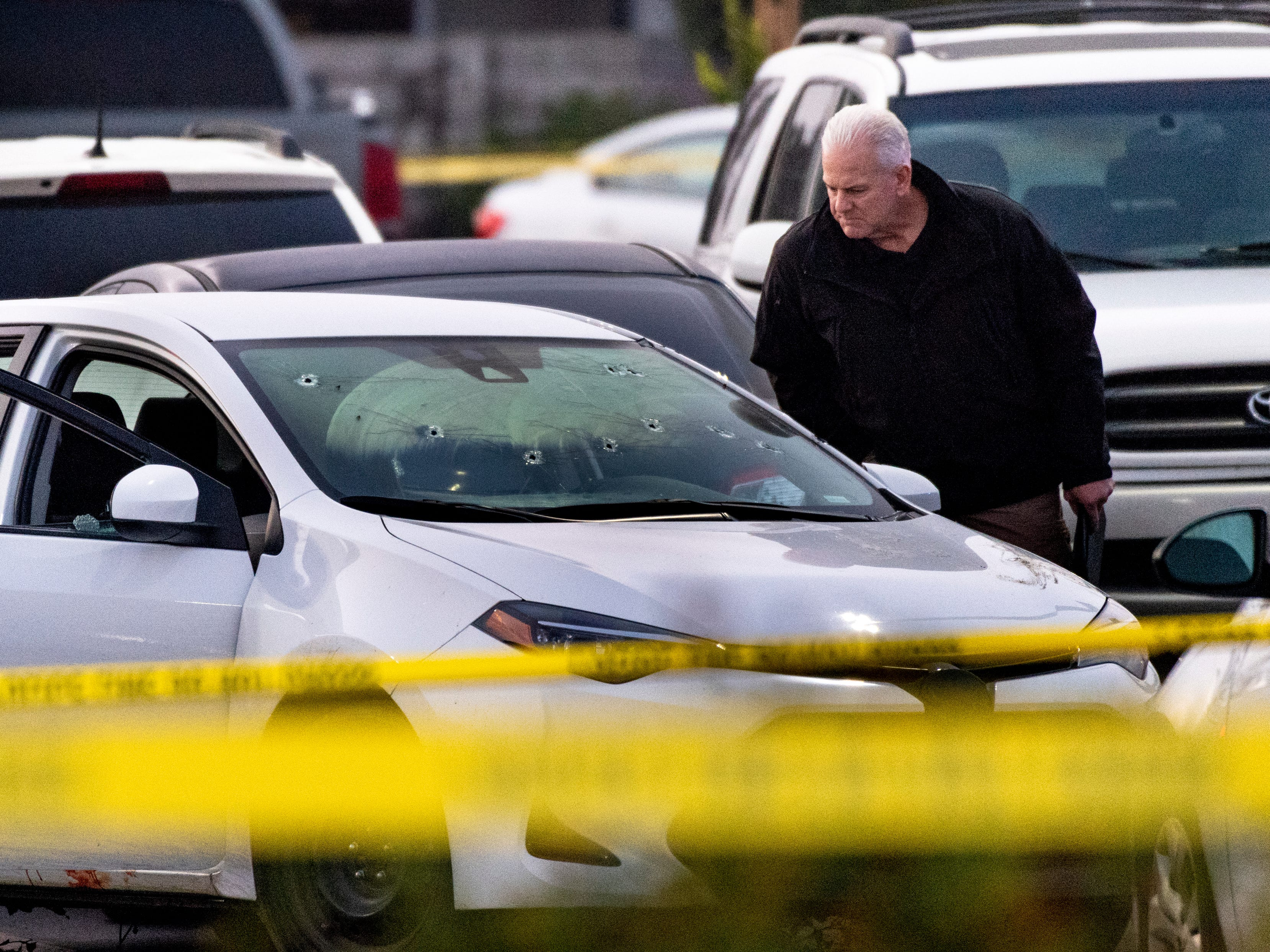 Visalia Police Lt. Ron Epp looks at the bullet-riddled car used by suspects during an officer-involved shooting in the north parking lot of Visalia Mall on Thursday, January 10, 2019.