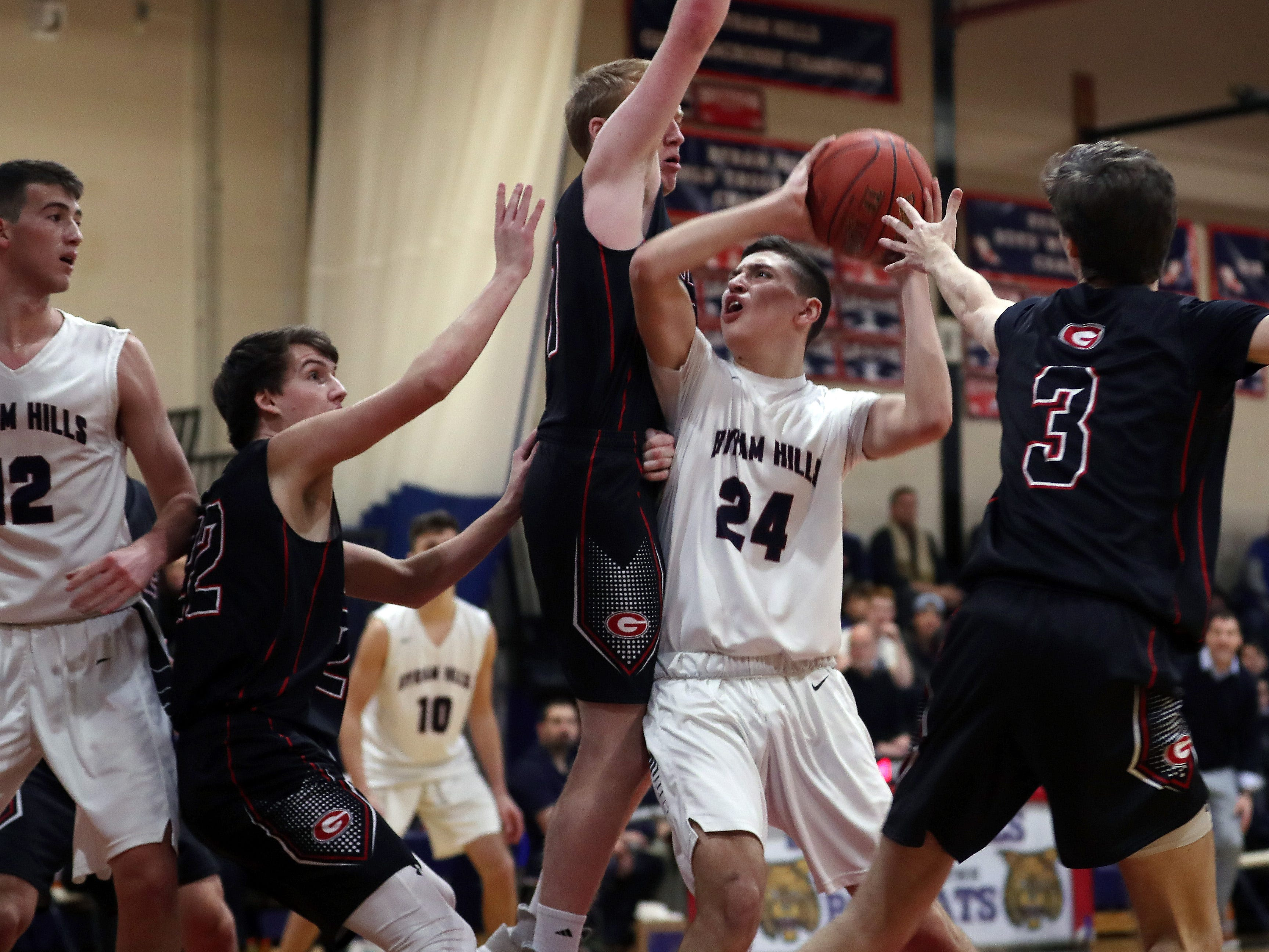 Byram Hills Mike Parrotta (24) drives to the basket in front orf Rye's Thomas Flaherty (21) during boys basketball action at Byram Hills High School in Armonk Jan. 10, 2019.
