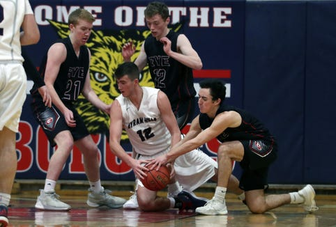 Byram Hills Ben Leff (12) battles for a loose ball with Rye's Thomas Flaherty (21) Sam Poole (22) and Troy Egan (5) Rye in boys basketball action at Byram Hills High School in Armonk Jan. 10, 2019.