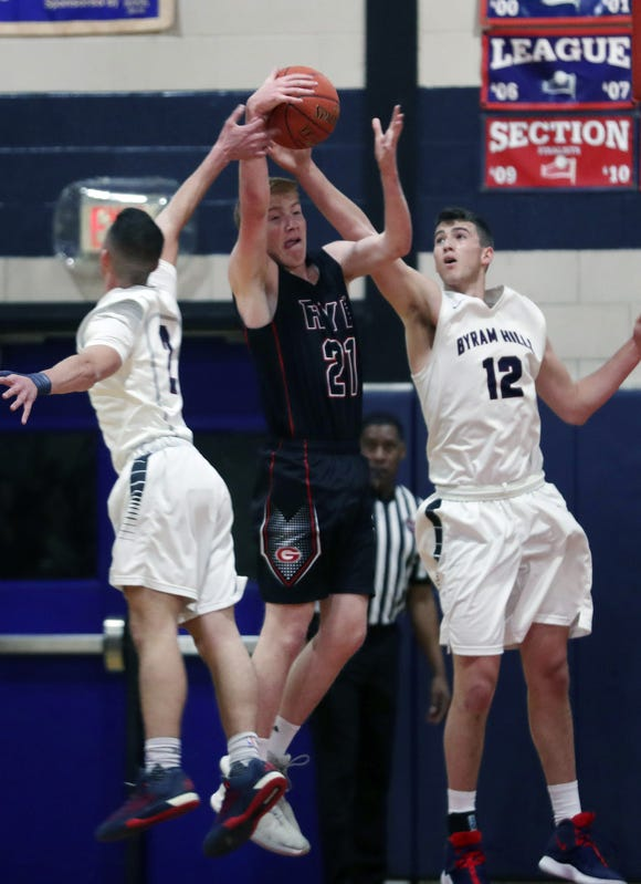 Rye's Thomas Flaherty (21) battles for a rebound with Byram Hills' Mike Kalion (2) and Ben Leff (12) during boys basketball action at Byram Hills High School in Armonk Jan. 10, 2019. Byram Hills won the game.