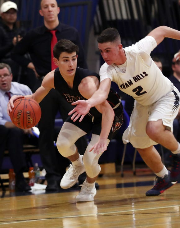 Rye's Matthew Tepedino (1) tries to get around Byram Hills' Mike Kalion (2) during boys basketball action at Byram Hills High School in Armonk Jan. 10, 2019. Byram Hills won the game.