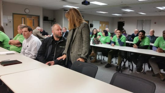 Bloom Energy officials have a discussion prior to the beginning of a DNREC public meeting in January 2019. Company employees wearing matching, light green shirts look on.