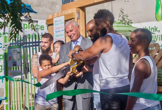 James L.A. Thompson, second from right, participates in the ribbon-cutting for Wilmgitnon Green Box with Wilmington Mayor Michael Purzycki