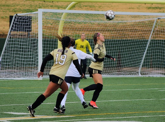 Freshman Lily Dodson  heads the ball towards the net against Keller Friday afternoon at Memorial Stadium.