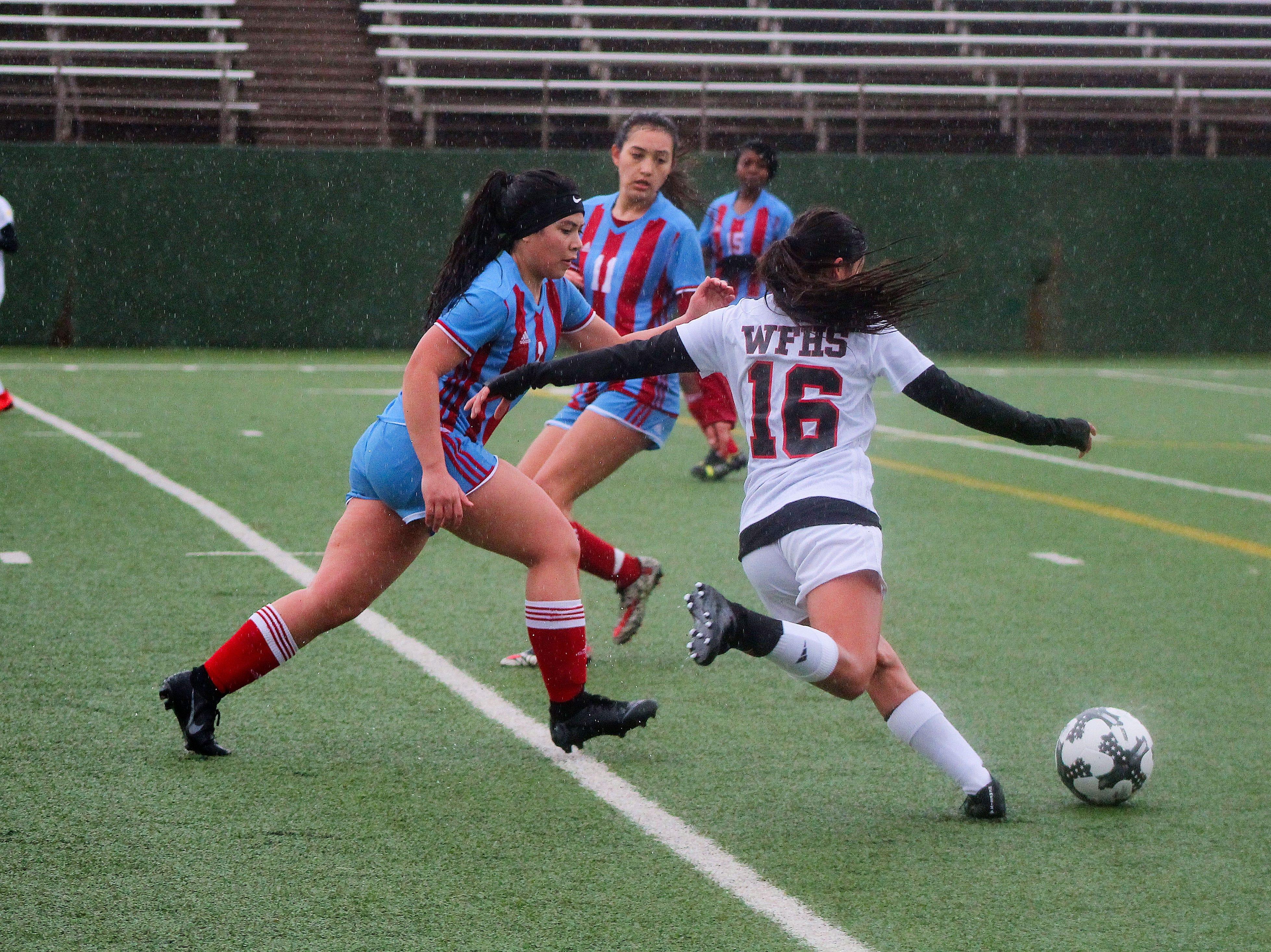 Freshman Jazel Sanchez strikes the ball for Old High as Hirschi's Ana De La Paz defends.