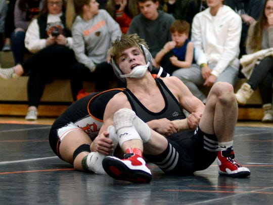 Sheridan's Deven Factor tries to escape from New Lexington's Kody Beal at 132 pounds. Beal won the match, 7-3.