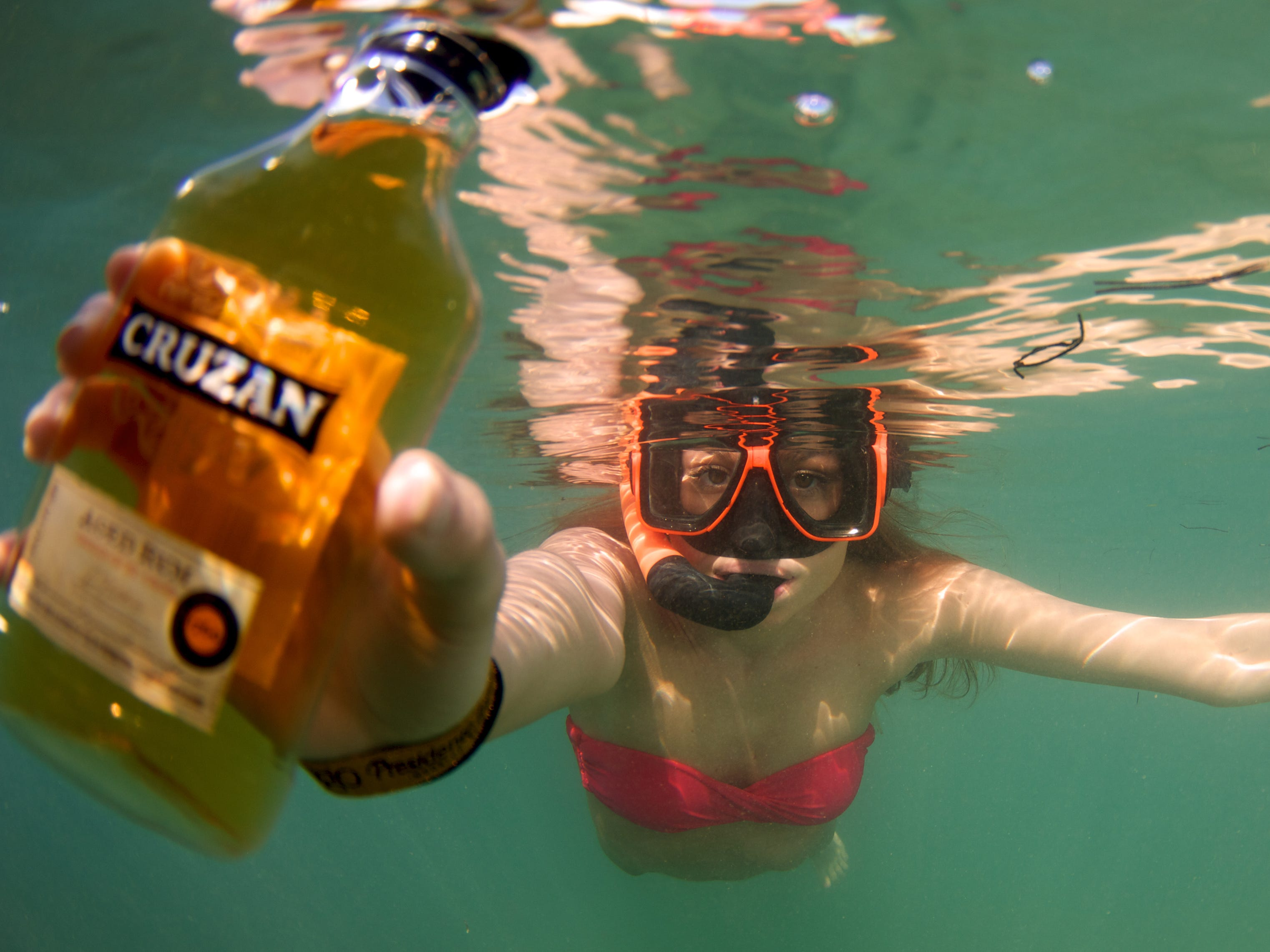 Donning snorkel gear, visitors comb the waters for hidden bottles of Cruzan Rum  distilled next door in St. Croix.