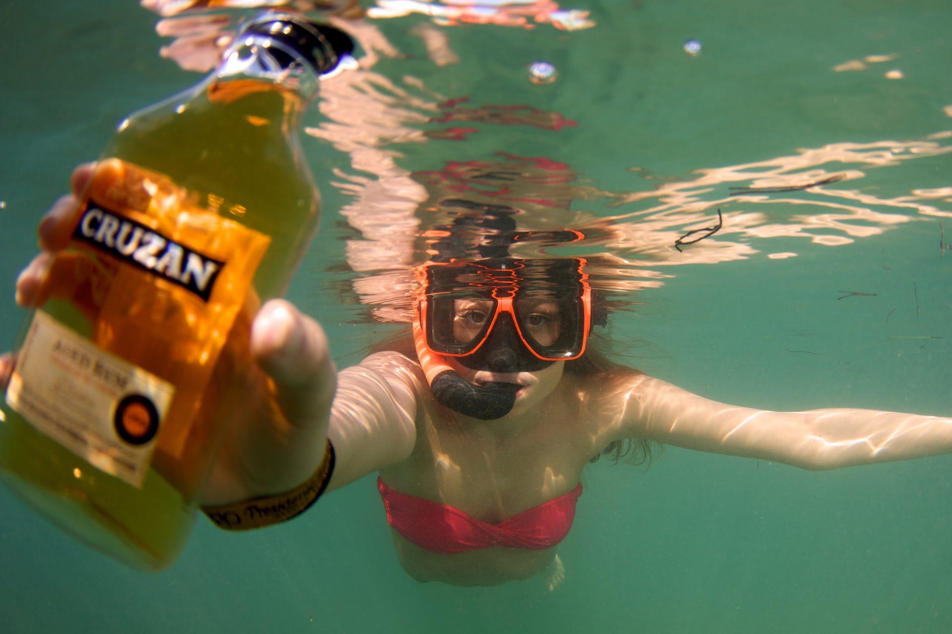 Donning snorkel gear, visitors comb the waters for hidden bottles of Cruzan Rum  distilled next door in St. Croix.