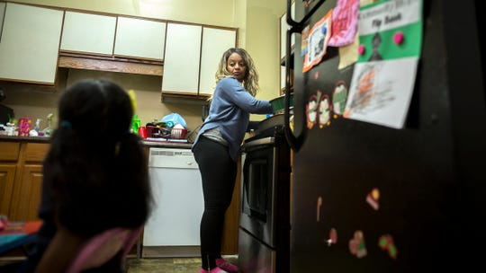 Latrelle Huff serves dinner for her children.
