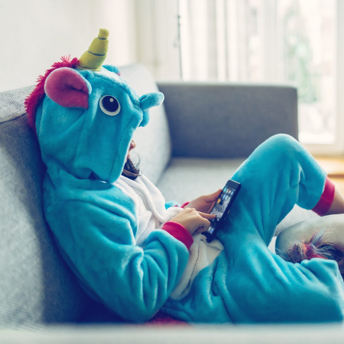 little girl in unicorn costume relaxing with mobile on couch at home
