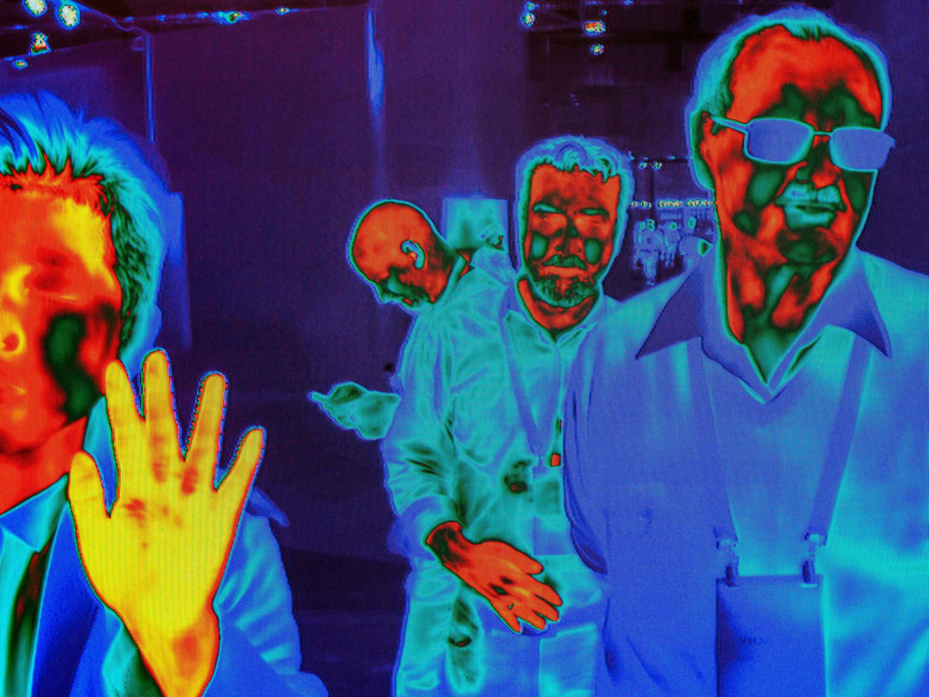 People are captured by FLIR (Forward-Looking Infrared) HD Thermal Imaging Cameras as they walk near the FLIR exhibit.