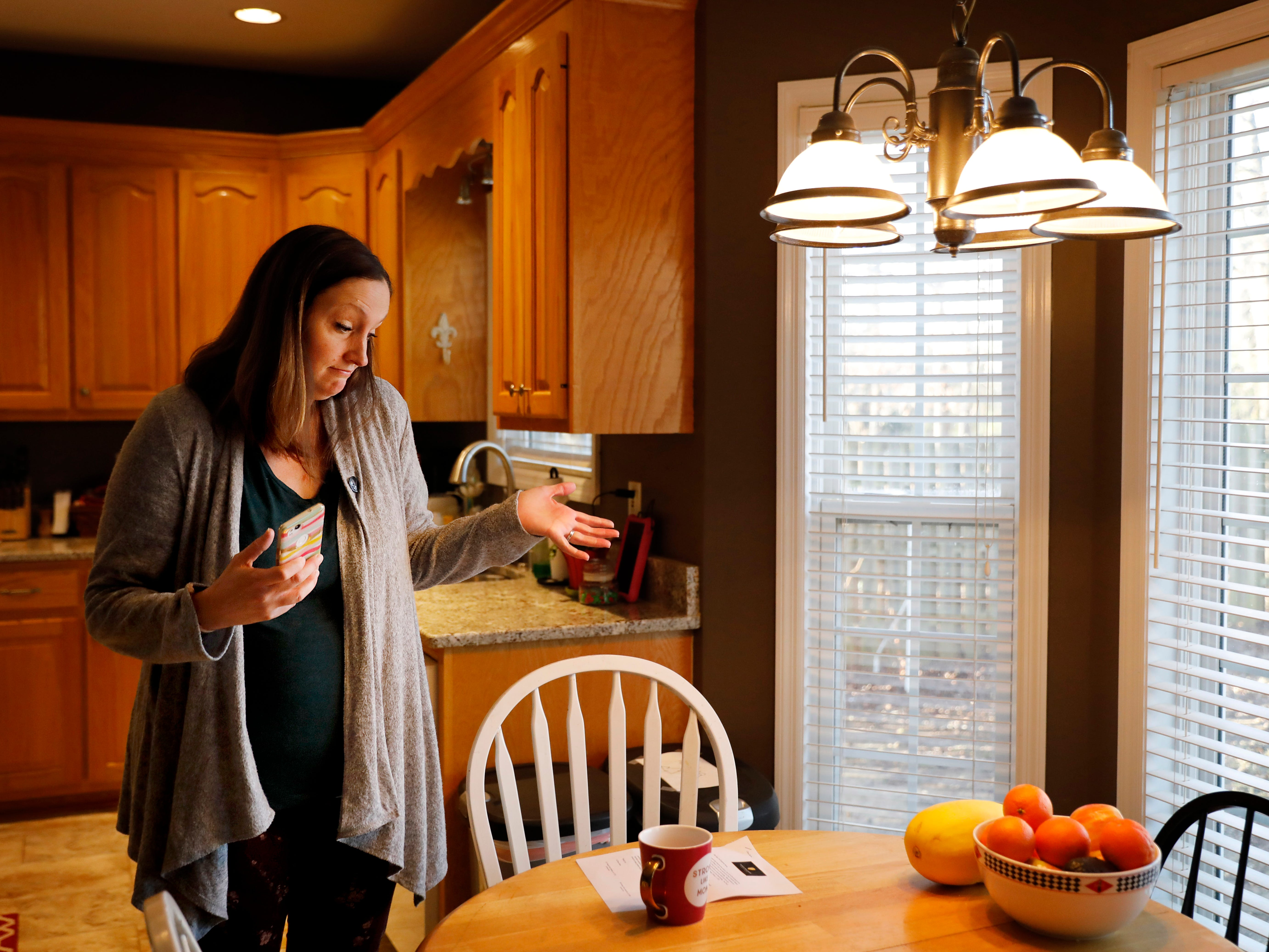 Katie Barron gestures while looking at a pay increase notice for her children's day care, in her home in Madison, Ala., Jan. 9, 2019. Barron's husband is a National Weather Service meteorologist forced to work without pay during the shutdown because his job is classified as essential. They've put off home and car maintenance, but the $450-a-week bill for day care still has to be paid, as do the mortgage and utility bills.