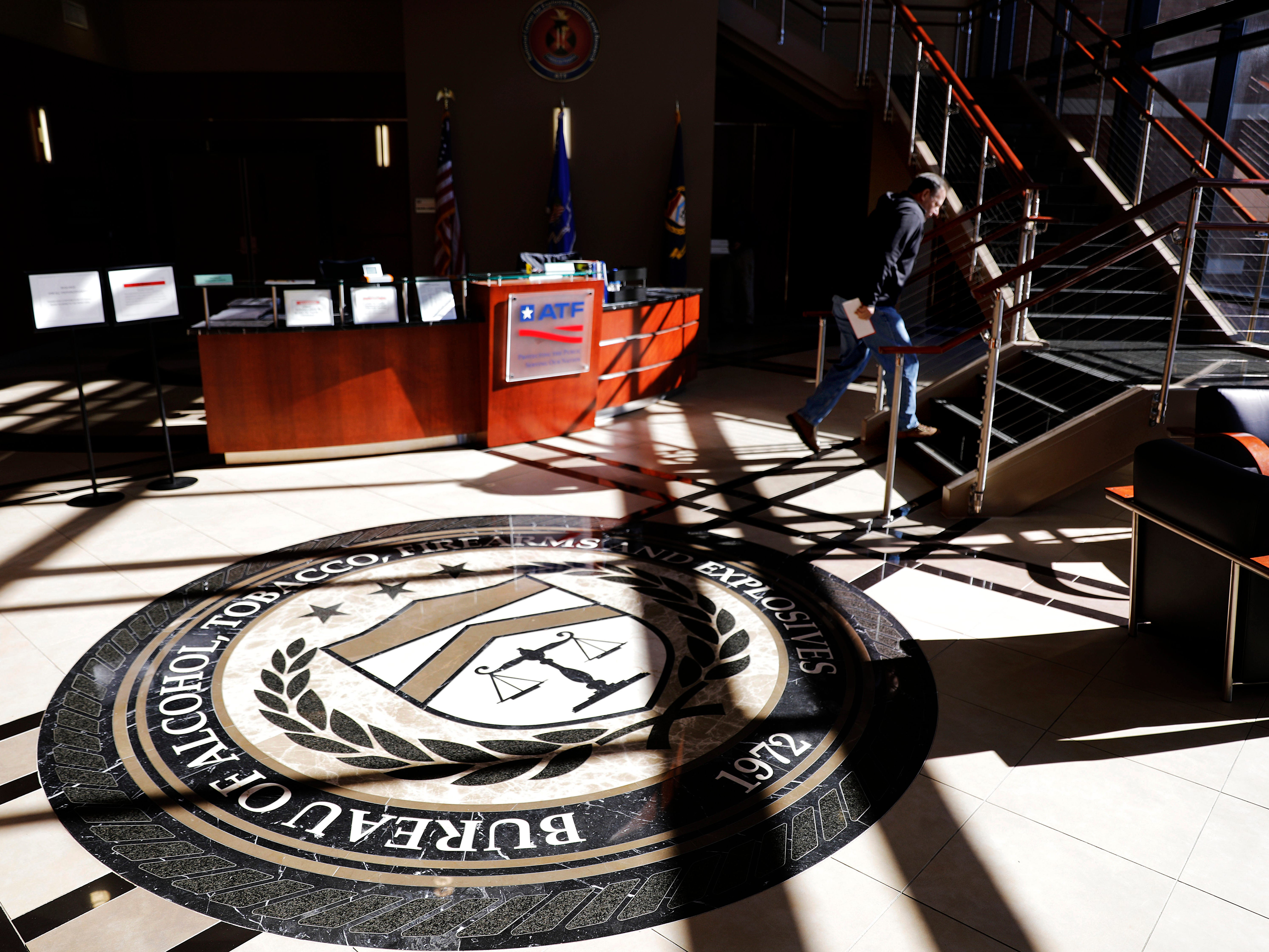 A worker walks through the empty lobby of the federal Bureau of Alcohol, Tobacco, Firearms and Explosives' National Center for Explosives Training and Research in Huntsville, Ala.,  Jan. 9, 2019. About 70 federal agencies are located at the Army's sprawling Redstone Arsenal, and more than half the area economy is tied to Washington spending.