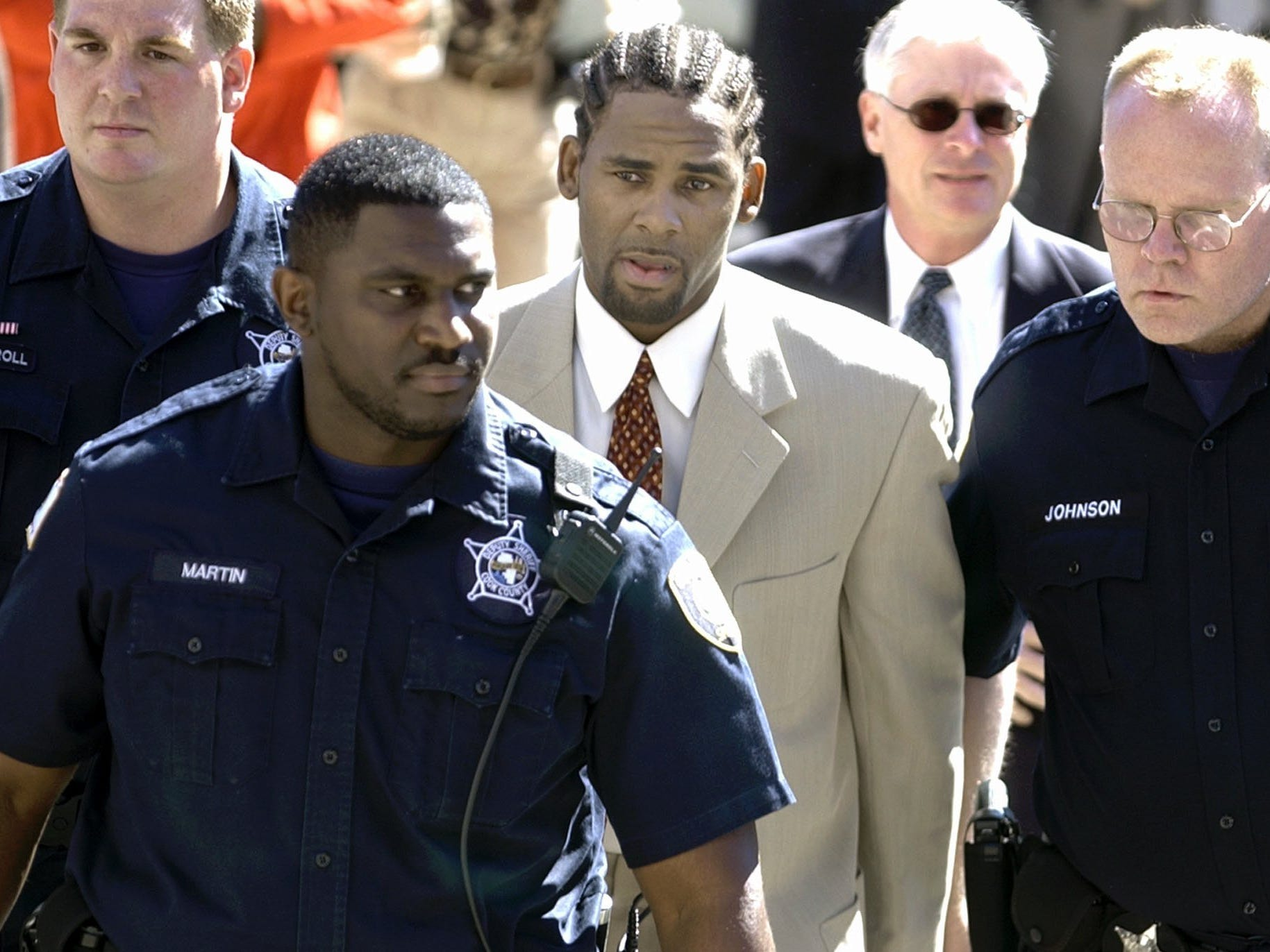 Police officials surround R. Kelly as he arrives at a Chicago court for an appearance on Aug. 7, 2002.  Kelly, a Chicago-area resident, is accused of appearing on a videotape that prosecutors say shows him sexually involved with an underage girl. Kelly has said the man on the tape is not him.