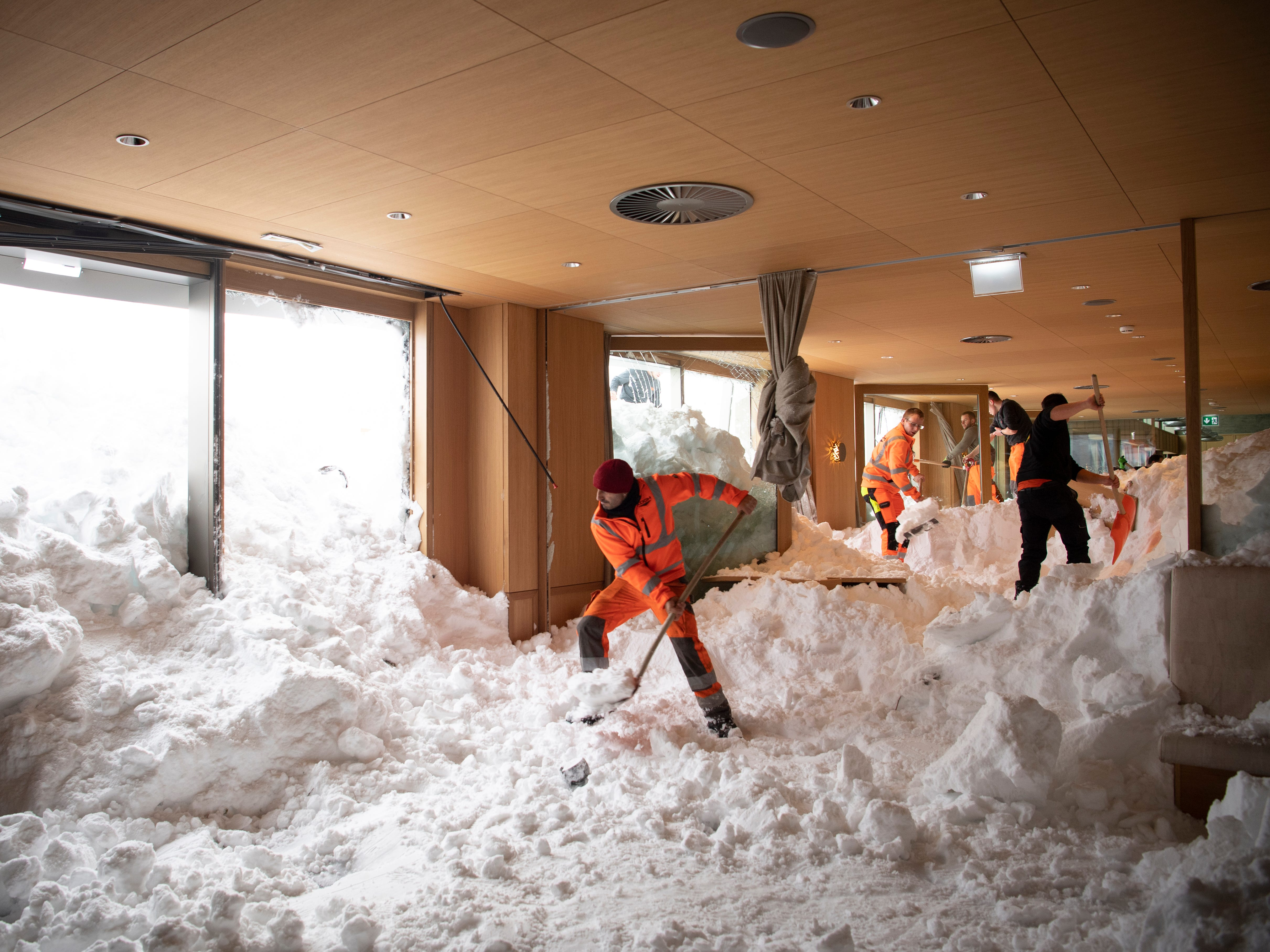 People clear snow from inside the Hotel Saentis in Schwaegalp, Switzerland, after an avalanche, Ajan 11. 2019. Police said three people were slightly hurt.