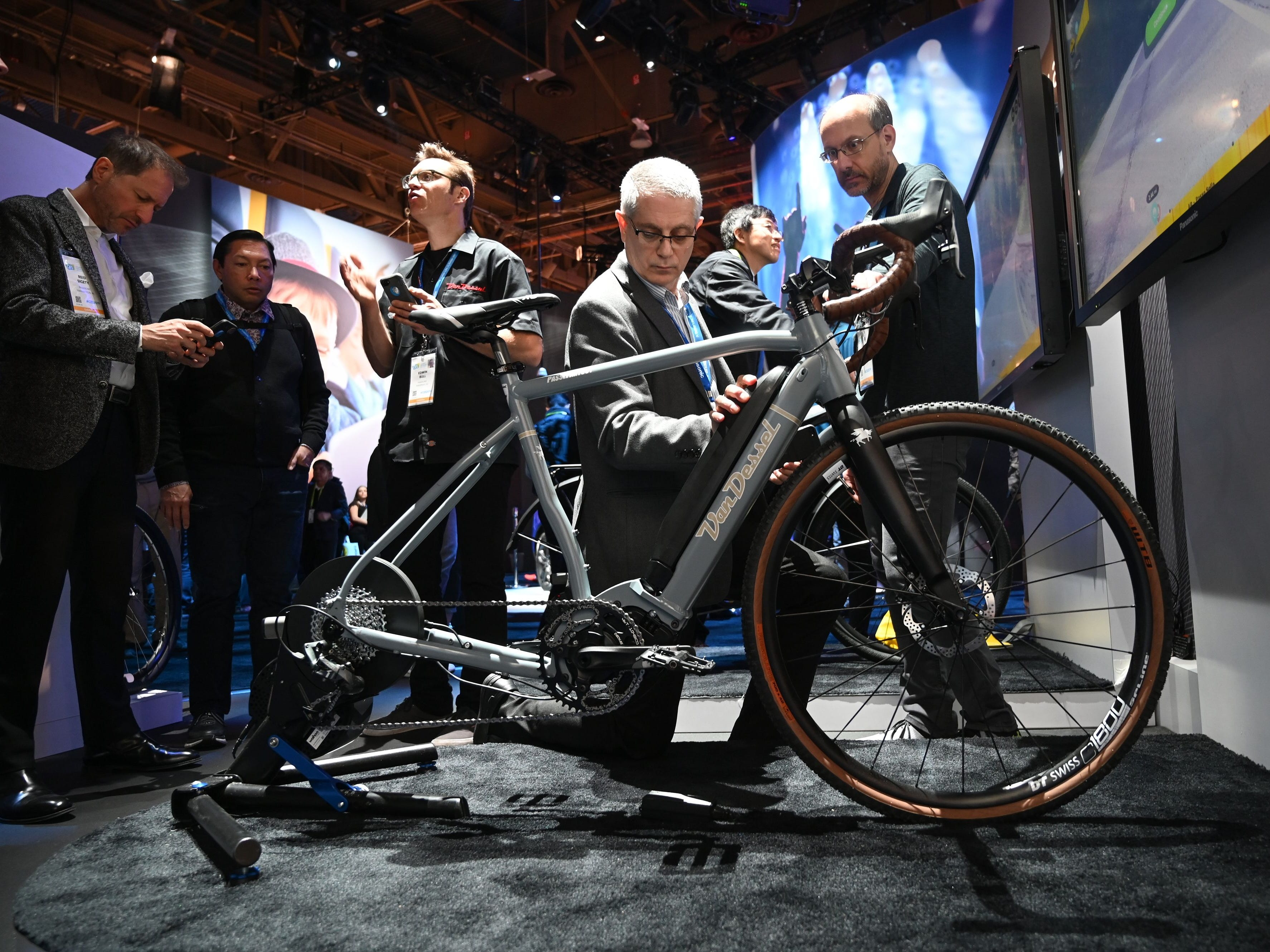 An attendee touches the batteries of a Van Dessel electric gravel bike.