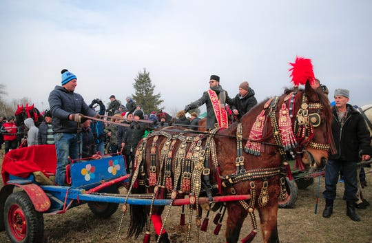 An Orthodox priest sprinkles holy water on horses and people during Epiphany celebrations in Pietrosani, Romania.