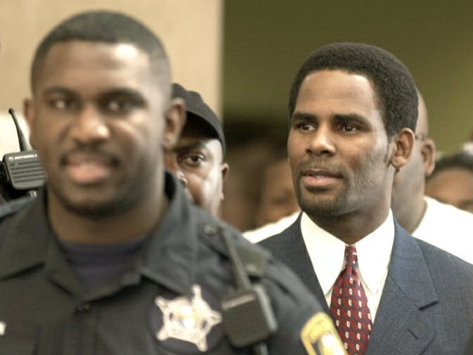 R. Kelly is escorted from a Chicago court  June 26, 2002, after entering a plea of innocent to child pornography charges.   Kelly is accused of appearing on a videotape that prosecutors say shows him sexually involved with an underage girl.
