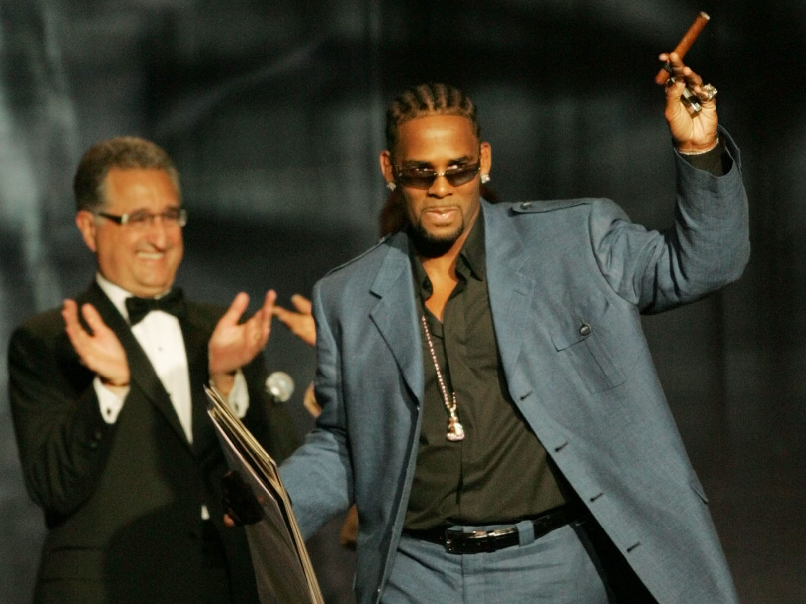 R. Kelly, right, acknowledges  the crowd as BMI President and CEO Del Bryant applauds after Kelly received a 2005 BMI Urban Music Award on Aug. 26, 2005, in Miami Beach, Fla. Kelly received several awards including a BMI Crystal as Urban Songwriter of the Year. He was also named one of BMI's top songwriter/producers.
